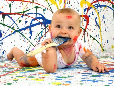 Foto artística de un niño pintando paredes con diferentes colores